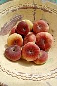 Fresh vineyard peaches in bowl (overhead view)