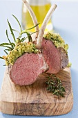 Lamb chops with herb crust on chopping board