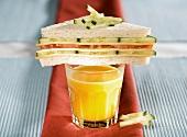 Tomato and cucumber tramezzini on a glass of orange juice