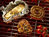 Fish in foil, meat, sausage and tomatoes on a barbecue