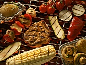 Vegetables, meat, mushrooms & corn on the cob on a barbecue