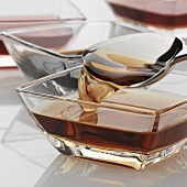 Various types of vinegar in glass dishes with spoon