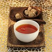 Rooibos tea in white bowl, brown sugar cubes behind