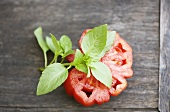Slice of tomato and a sprig of basil