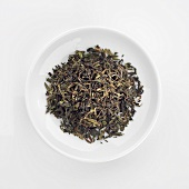 Organic Darjeeling tea leaves in dish (overhead view)