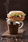 Bagel filled with turkey ham on coffee cup
