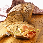 Linseed bread, partly sliced, raw ham on one slice