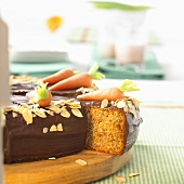 Carrot cake with marzipan carrots, a piece partly removed