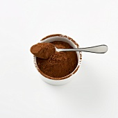 Cocoa powder in small dish with spoon