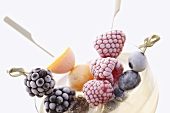 Frozen fruit skewers in a saucer of champagne