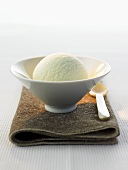 A scoop of tea ice cream in a bowl on brown cloth