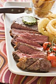 Beef steak with herb butter and deep-fried onion rings