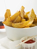 Potato wedges in white bowl, ketchup beside it