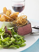 Beef fillet with salad leaves, potato wedges, glass of red wine