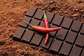 Bar of chocolate and two red chillies on cocoa powder