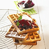 Amaranth waffles with fruit and cream on cake rack