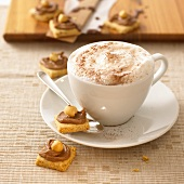Cup of cappuccino and hazelnut biscuits