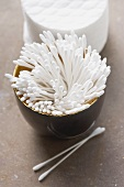 Cotton buds in a bowl, cotton wool pads behind