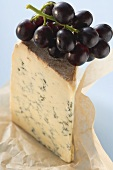Piece of Stilton with red grapes on paper
