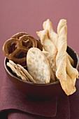 Crackers, salted pretzels, breadsticks in brown bowl