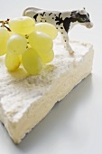 Piece of Brie with green grapes and toy calf