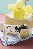 Brie with green grapes, toy calf in foreground