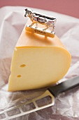 Piece of Gouda cheese with label and cheese knife