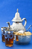 Two glasses of black tea, biscuits and silver teapot