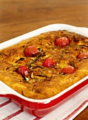Focaccia with rosemary and tomatoes in a baking dish