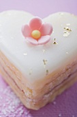Small heart-shaped cake with sugar flower and gold leaf