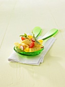 Pasta salad with radishes and tomatoes on salad servers