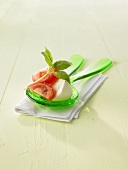 Tomatoes with mozzarella and basil on salad servers