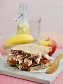 Sandwich mit Hähnchen, im Hintergrund Obst und Getränk