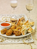 Assorted party snacks with dip, glasses of sparkling wine