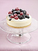 Mixed berry cheesecake with icing sugar on cake stand