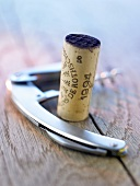 Wine cork and corkscrew on wooden background