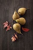 Pears and autumn leaves on wooden background