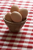 Eggs in brown basin on checked tablecloth