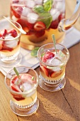 Strawberry punch with basil in glasses and glass jug