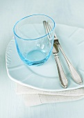 Empty glass and cutlery on white plate