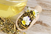 Field pansy tea and tea leaves in scoop