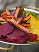 Salad ingredients in colander (beetrot, yellow beet, carrots)