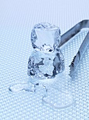 Two ice cubes with ice tongs