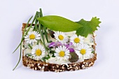 Wholemeal bread with herb butter and daisies