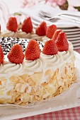 Strawberry cream cake with flaked almonds (detail)