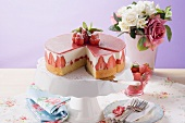 Strawberry yoghurt cake, a piece cut, on cake stand
