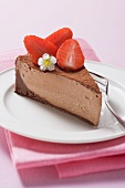 Piece of chocolate cheesecake with strawberries & cocoa powder