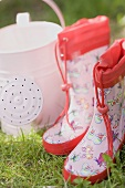 Child's rubber boots and watering can on grass