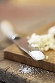 Salt on a knife tip, chopped garlic beside it