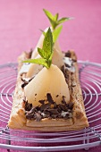 Puff pastry pear tart with grated chocolate on cake rack